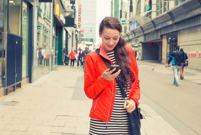 Bigstock  Happy girl texting on the smart phone walking down the street wearing a red jacket in autumn