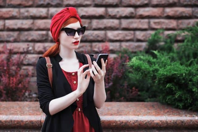 Stylish red-haired girl in sunglasses and in a red turban with a mobile phone in her hands. A woman with a new phone. Black phone in hand. The girl is looking at the phone. Internet on the phone. Touchscreen phone
